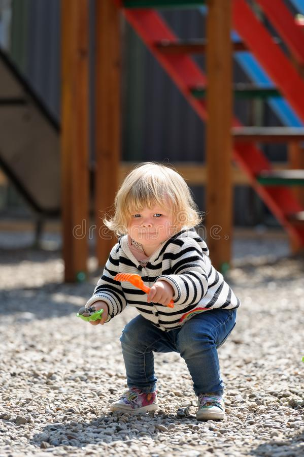 Cute toddler baby girl playing with shovel at playground royalty free stock photography
