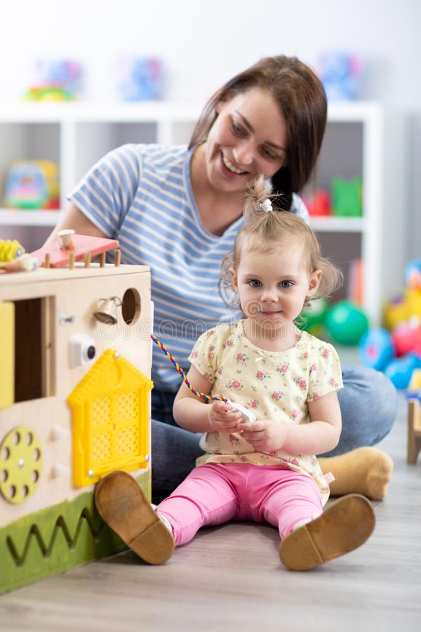 Cute toddler baby playing with busyboard. Mother or babysitter teaching kid in nursery. Children`s educational toys. Cute toddler baby playing with busyboard royalty free stock image