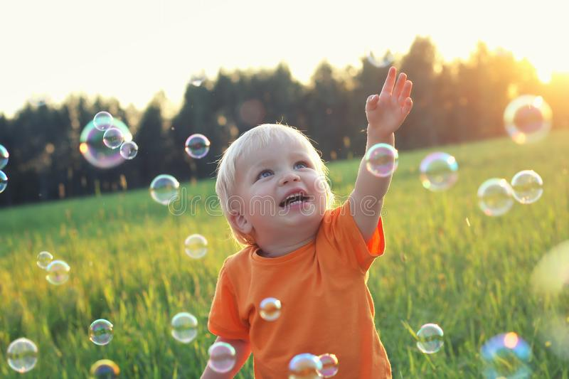 Cute toddler blond boy playing with soap bubbles on summer field. Happy child summertime concept. Authentic lifestyle image stock photography