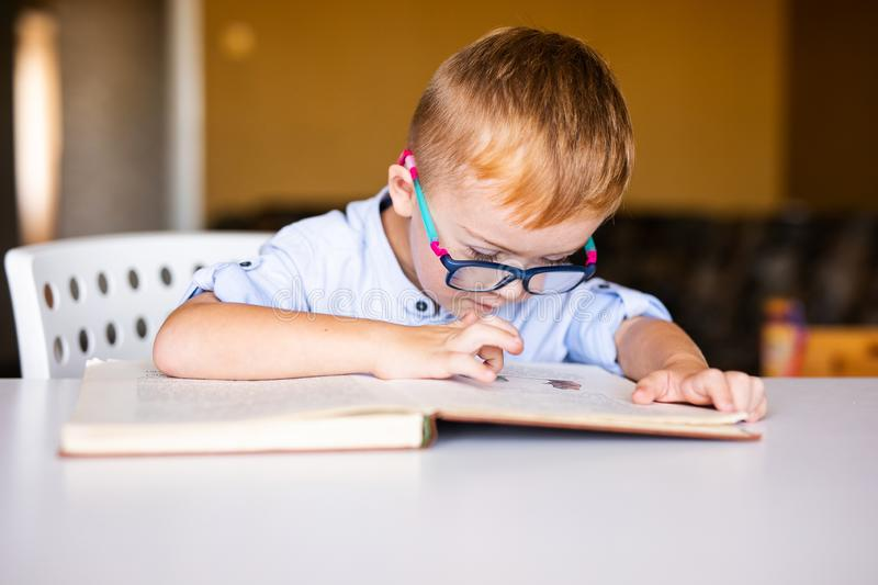 Cute toddler boy with down syndrome with big glasses reading intesting book.  royalty free stock photography