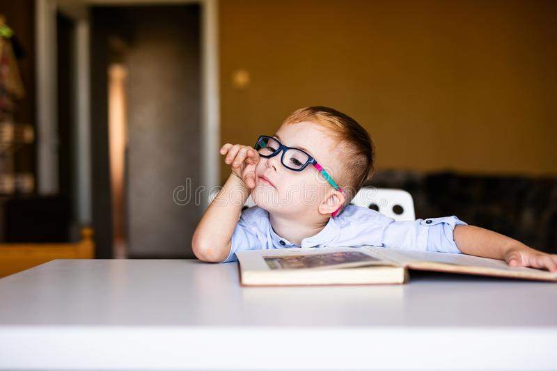 Cute toddler boy with down syndrome with big glasses reading intesting book.  royalty free stock images