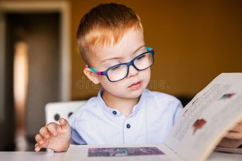 Cute toddler boy with down syndrome with big glasses reading intesting book.  stock images