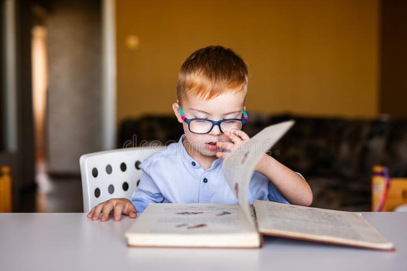 Cute toddler boy with down syndrome with big glasses reading intesting book.  stock photography