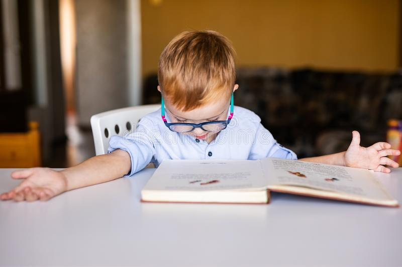 Cute toddler boy with down syndrome with big glasses reading intesting book.  royalty free stock image
