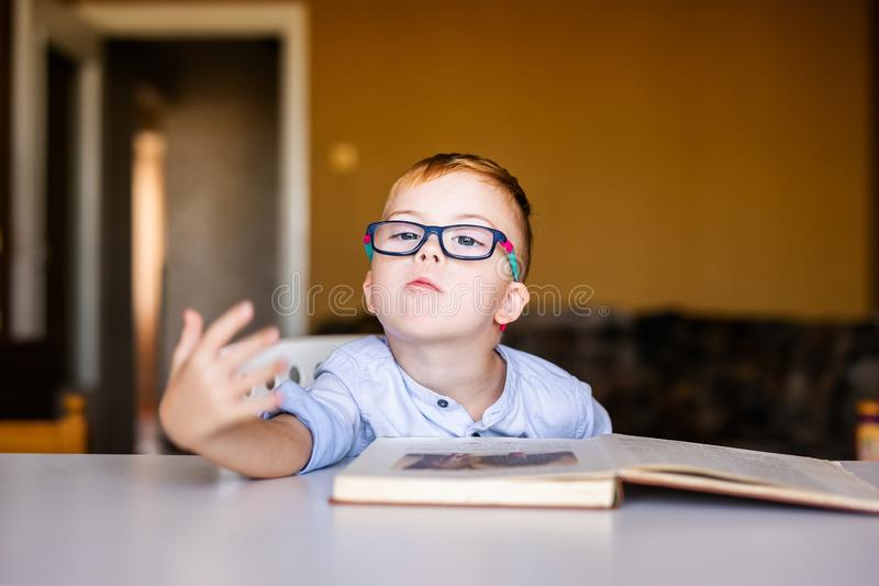 Cute toddler boy with down syndrome with big glasses reading intesting book.  royalty free stock photo
