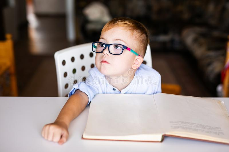 Cute toddler boy with down syndrome with big glasses reading intesting book.  royalty free stock photos