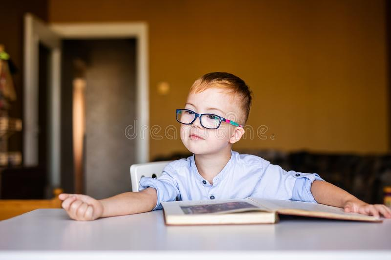 Cute toddler boy with down syndrome with big glasses reading intesting book.  stock image