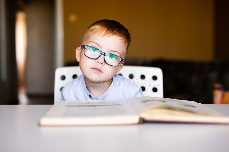 Cute toddler boy with down syndrome with big glasses reading intesting book.  stock photos