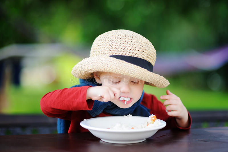 Cute toddler boy eating rice cereal outdoors stock photography