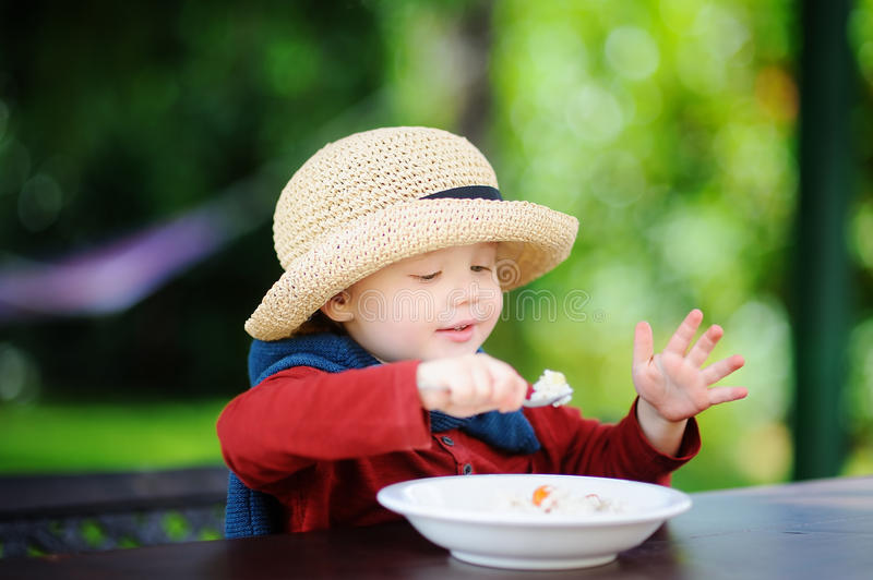 Cute toddler boy eating rice cereal outdoors royalty free stock photography