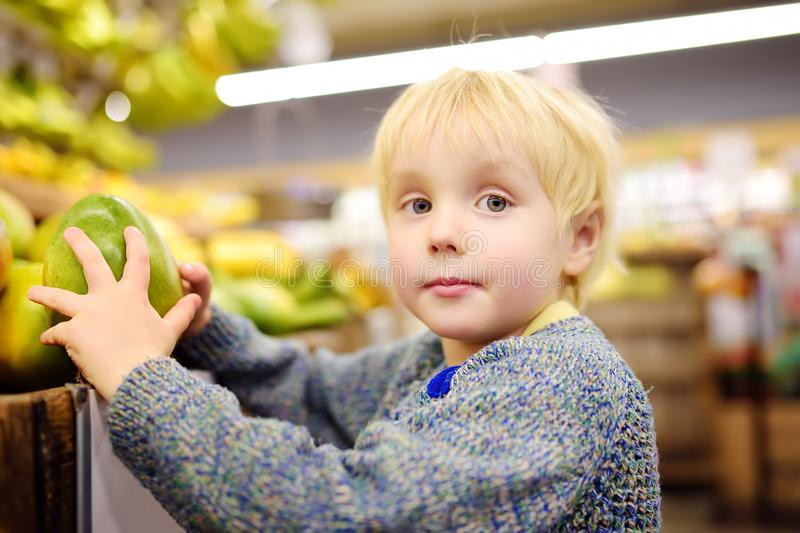 Cute toddler boy in a food store or a supermarket choosing fresh organic mango. Healthy lifestyle for young family with kids royalty free stock photo