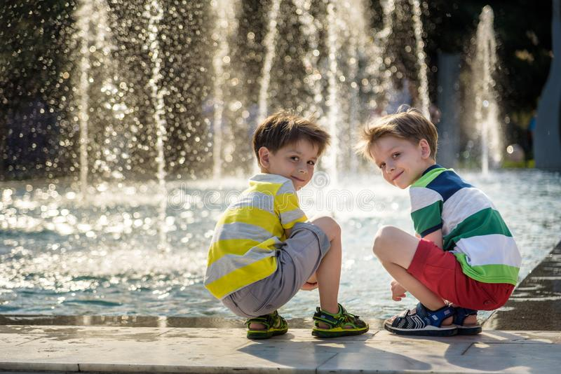 Cute toddler boy and older brothers, playing on a jet fountains with water splashing around, summertime stock photography