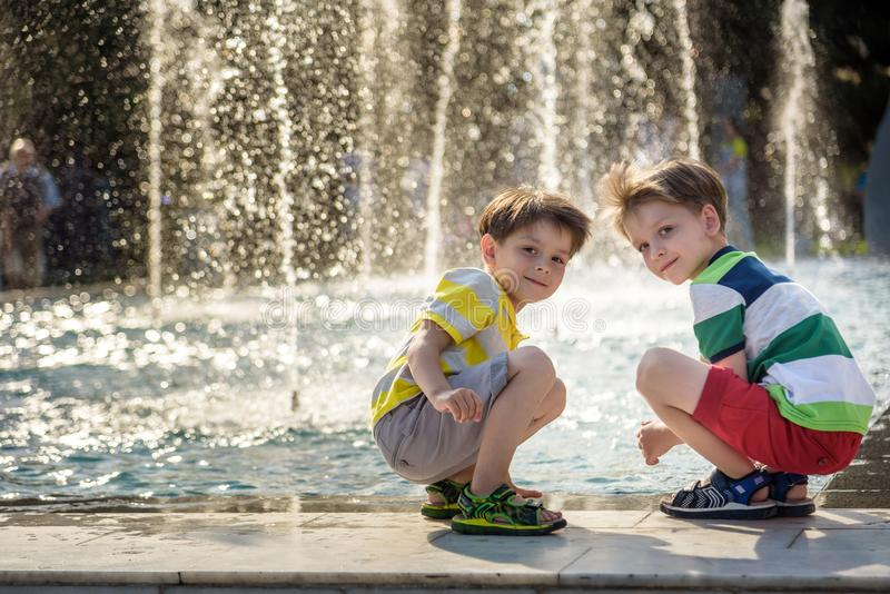 Cute toddler boy and older brothers, playing on a jet fountains with water splashing around, summertime stock images