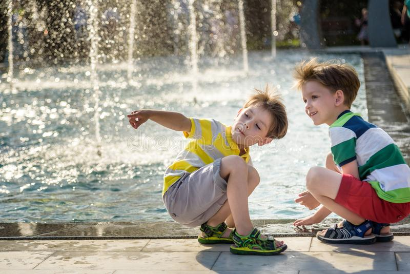 Cute toddler boy and older brothers, playing on a jet fountains with water splashing around, summertime stock photo