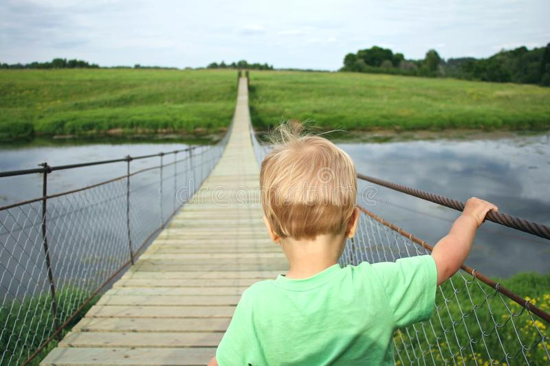 Cute toddler boy overcoming fear, prepering to crossing suspension bridge. Face your fears, look into the future, opening a new w royalty free stock image