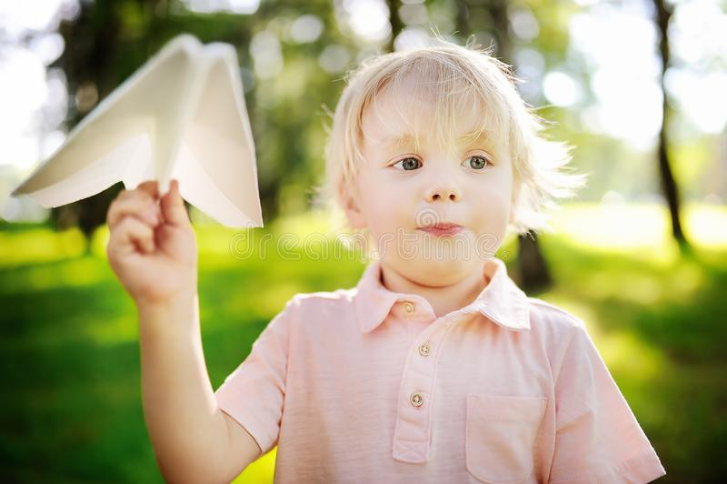 Cute toddler boy playing with paper plane in a summer park stock images