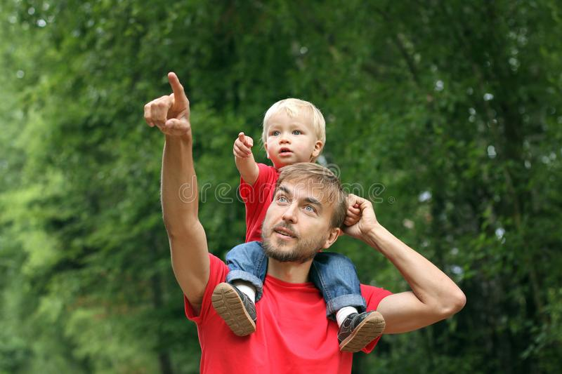 Cute toddler boy sits on his father`s shoulders. They point fingers in the same direction. Fatherhood concept. Family look clothi. Ng stock photos
