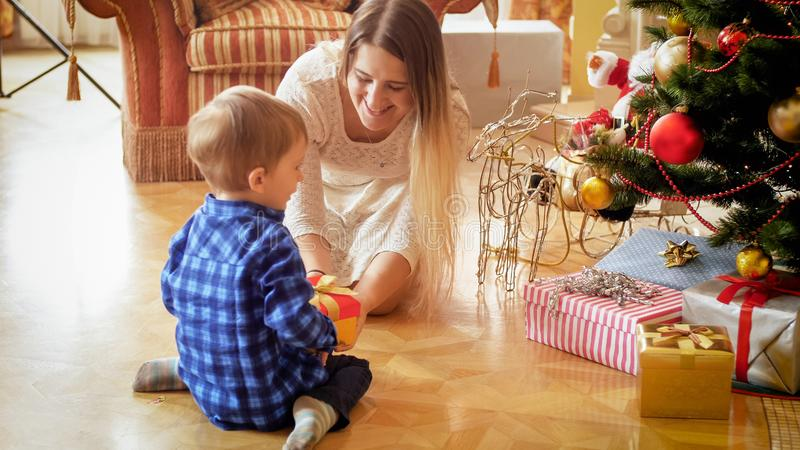 Cute toddler boy sitting on floor with mother and receiving Christmas gift stock photos