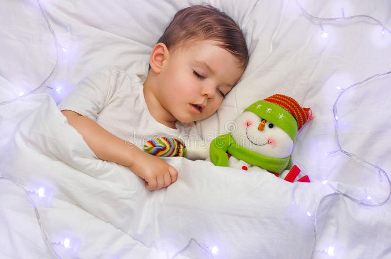 A cute toddler boy is sleeping on white linen with his favorite toy snowman in the blue lights of the garland. New year night stock image