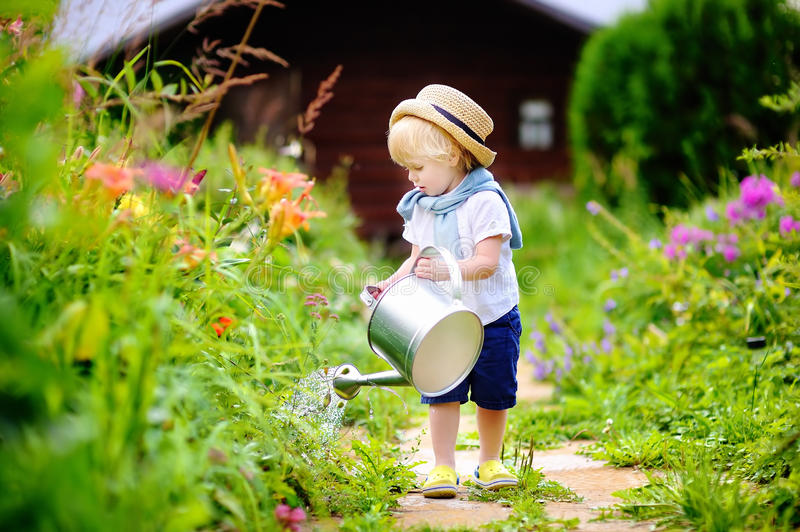 Cute toddler boy in straw hat watering plants in the garden stock images