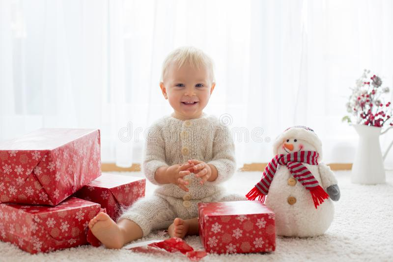 Cute toddler boy, sweet baby, opening presents at home royalty free stock photos