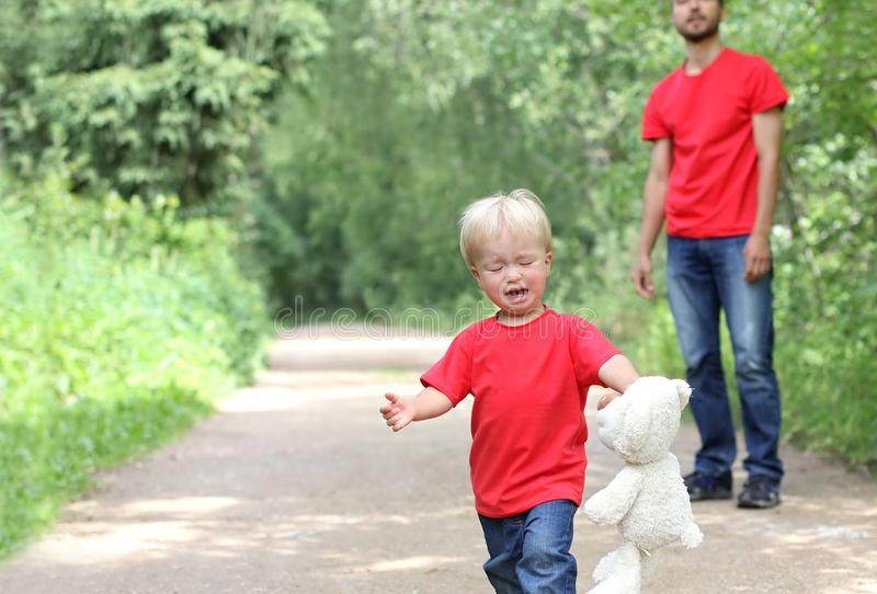 Cute toddler boy with a teddy bear in his arms is crying. Dad is standing behind. Parenting difficulties concept. Family look clot stock photo