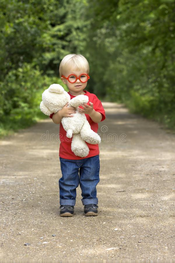 Cute toddler boy with toy glasses and plush bear standing on rural road. Little baby outdoor royalty free stock photography