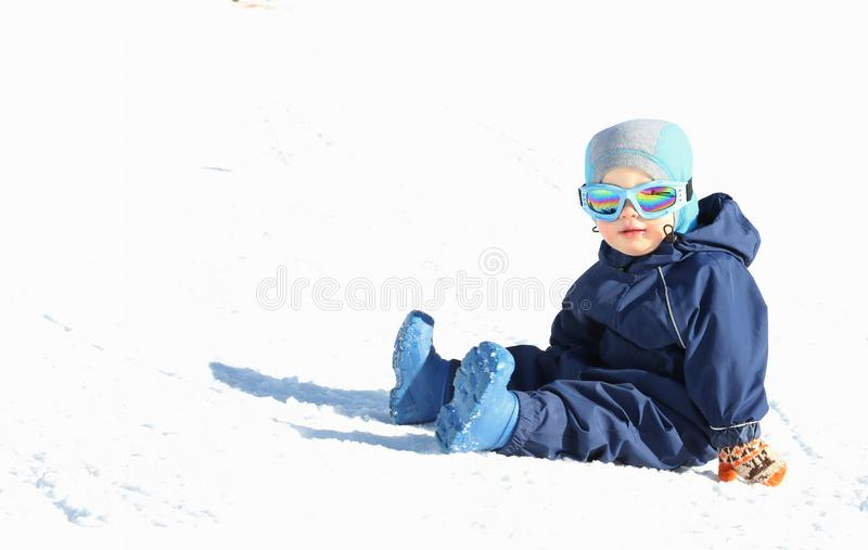 Cute toddler boy in winter suit and ski glusses sits on snow slope on sunny day. Copy space stock photo
