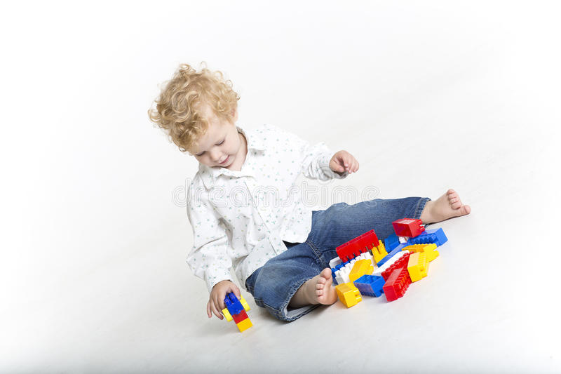 Cute toddler is building with legos stock photos