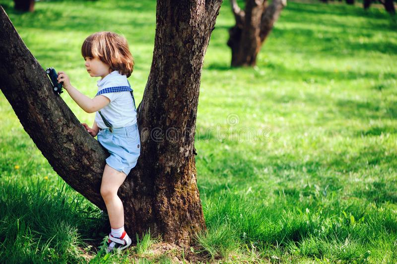 Cute toddler child boy with long hair in stylish outfit playing with toy car on the walk in summer royalty free stock photos