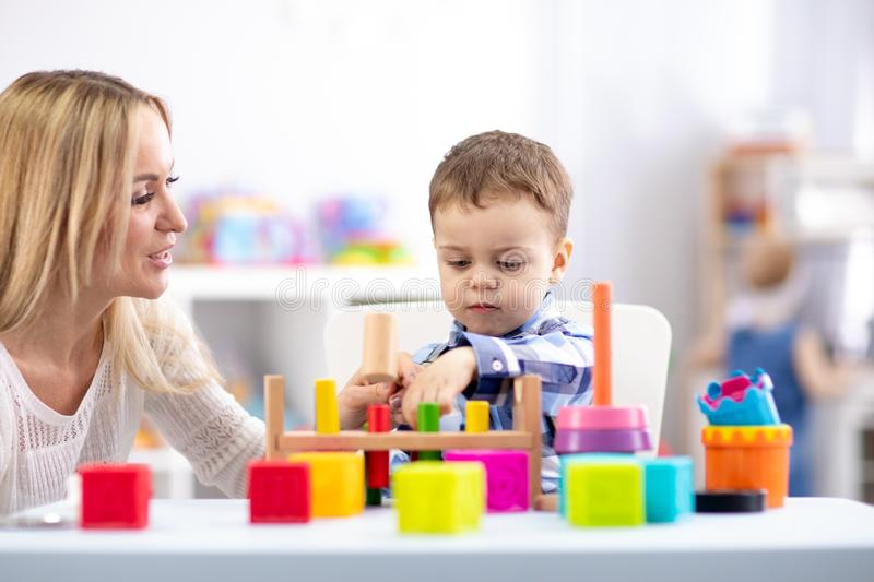 Cute toddler baby playing with wooden hammer block toy. Woman mother or teacher teaching kid in nursery stock images