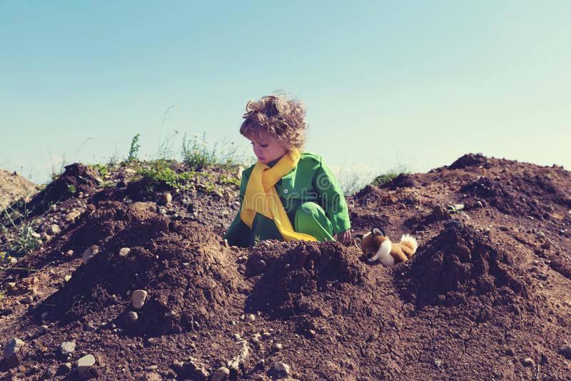 Cute toddler with curly blond hair playing with plush fox toy above pile of earth wearing green and yellow clothes. Selective focus stock images