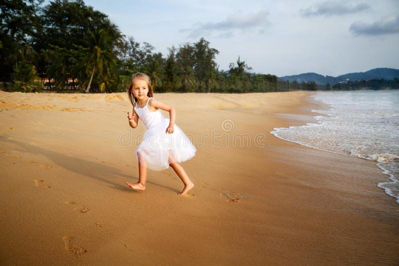 Cute toddler girl with blonde hair in a white tutu dress running on a sandy beach at sunset. Happy childhood memories royalty free stock photos