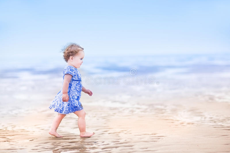 Cute toddler girl in blue dress walking on beach. Cute toddler girl in a blue dress walking on a beach at sunset stock photography