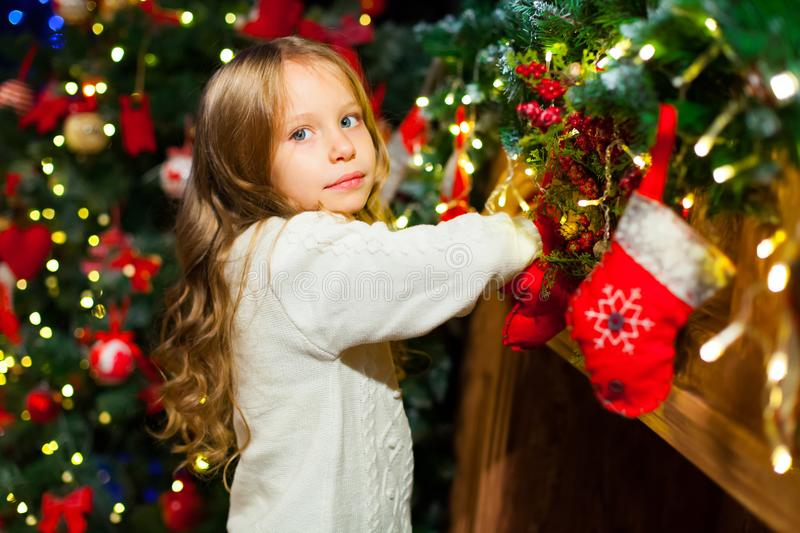 Cute toddler girl checking her Christmas stocking under a beauti stock images