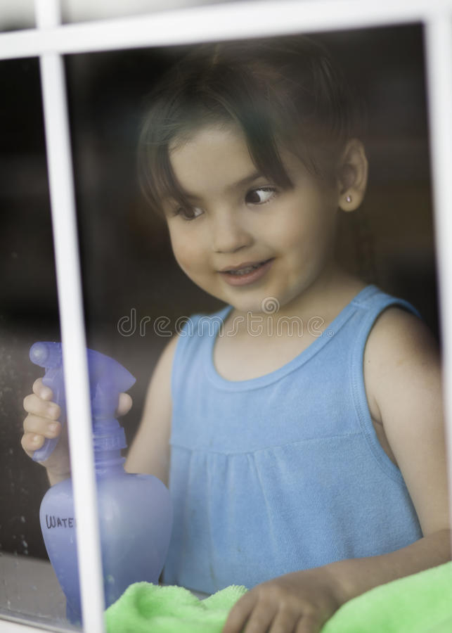 Cute Toddler Cleaning Window stock images