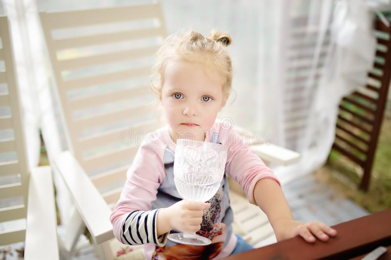 Cute toddler girl drinking still water from a beautiful glass royalty free stock image