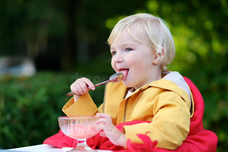 Cute toddler girl eating ice cream outdoors in cafe stock photography