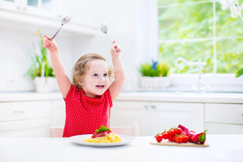Cute toddler girl eating spaghetti in a white kitchen royalty free stock images