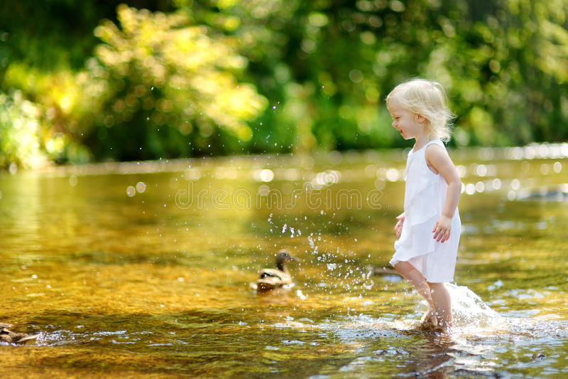 Cute toddler girl having fun by a river stock images