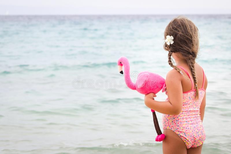 Adorable toddler girl with her favorite flamingo toy on tropical beach. Vacation and travel with kids concept stock photo