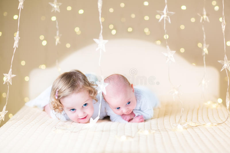 Cute toddler girl and her little newborn baby brother with warm soft lights stock images