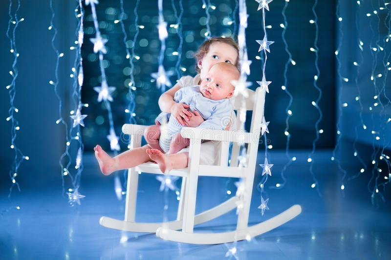 Cute toddler girl and her newborn baby brotherin a dark room with Christmas lights stock image