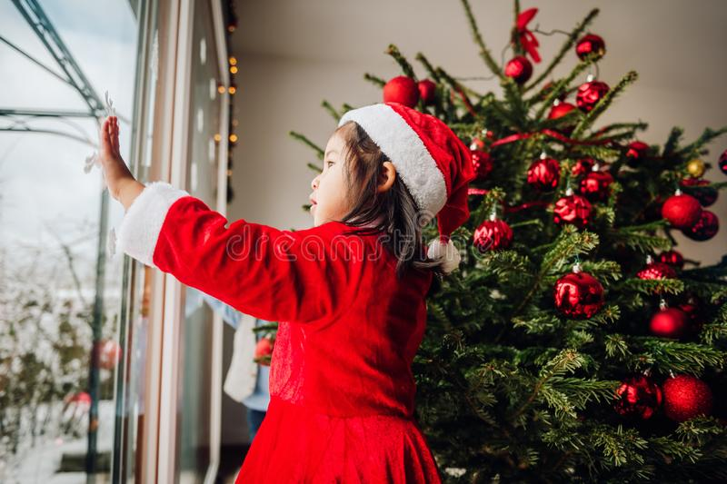 Cute toddler girl looking at the window at Christmas time. Wearing Santa dress and hat stock image