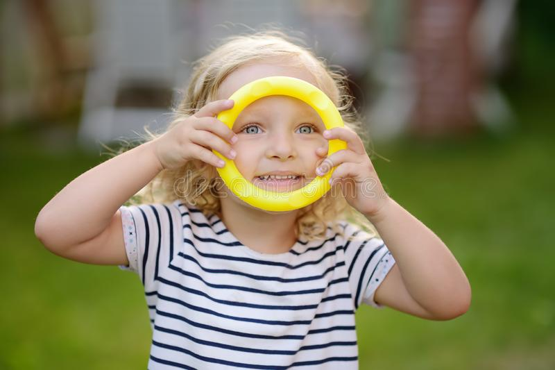 Cute toddler girl outdoors portrait in summer day. Child playing in game throwing rings at summer outdoors royalty free stock images