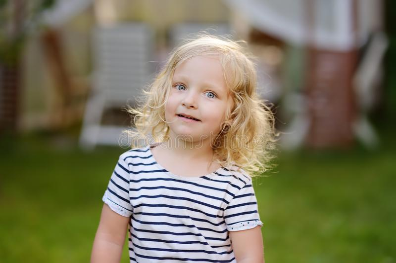 Cute toddler girl outdoors portrait in summer day. Smiling and charming child royalty free stock image
