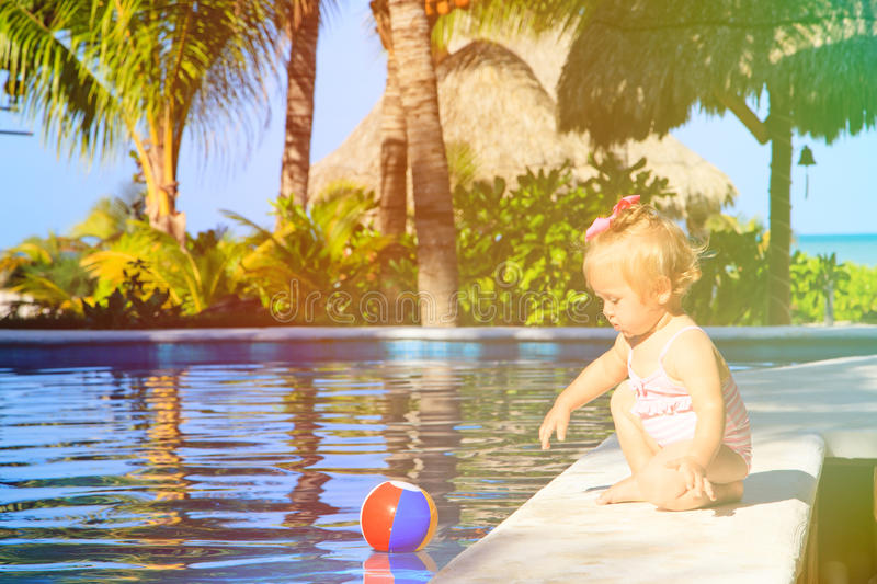 Cute toddler girl playing with ball in swimming. Cute toddler girl playing in swimming pool at tropical beach stock photos