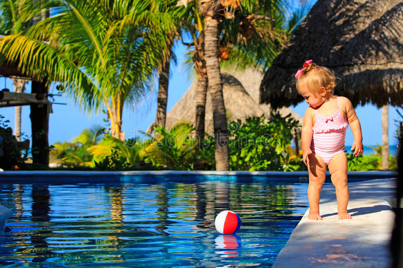 Cute toddler girl playing with ball in swimming. Cute toddler girl playing in swimming pool at tropical beach stock photo