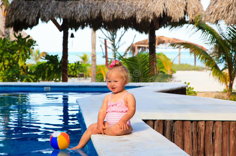 Cute toddler girl playing with ball in swimming. Cute toddler girl playing in swimming pool at tropical beach royalty free stock photo