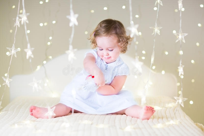 Cute toddler girl playing with her toy bear between soft lights in star shape. Sweet toddler girl in a white dress with beautiful curly hair playing with her toy royalty free stock photo